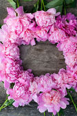 Peonies frame on wooden background — Stock Photo