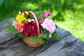 Roses in basket on garden table — Stock Photo