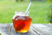 Honey jar on wooden table — Stock Photo