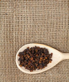 Cloves in wooden spoon on sackcloth — Stock Photo