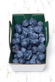Blueberries in a box on wooden table — Stok fotoğraf