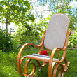 Rocking chair with rose and laptop in spring garden — Stock Photo