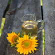 Stock Photo: Sunflower and sunflower oil on wooden table