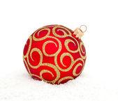 Red Chritsmas Ball lying on snow — Stock Photo