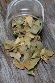 Bay leafs on wooden surface — Stock Photo