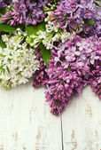 Lilac flowers on wooden table — Stock Photo