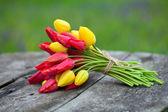 Svázané žluté a červené tulipány na dřevěné desce — Stock fotografie