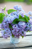 Bucket with lilac flowers on wooden garden table — Stock Photo