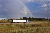 Semi truck driving under the rainbow — Stock fotografie