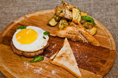 Scrambled eggs on meat with fried potatoes and toast — Stock Photo
