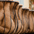 Row of empty garden wire baskets with liners in a garden shop — Stock Photo