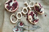 """Houten teken """"koken"""" gefotografeerd met helften van granaatappels en — Stockfoto"""