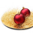 Christmas baubles on golden plate, isolated. — Stock Photo