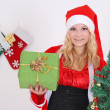 Woman in santa claus costume with presents and tree -  