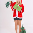 Woman in santa claus costume with gift and tree — Stock Photo
