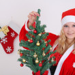 Woman in santa claus costume with presents and tree — Stock Photo #14035047