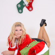 Blonde in santa costume with gift — Stock Photo