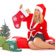 Woman in santa claus costume with presents and tree — Stock Photo