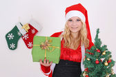 Woman in santa claus costume with presents and tree — ストック写真