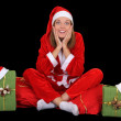 Surprised girl in santcostume with presents — Stockfoto #14137731
