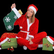Happy girl in santa costume sitting with presents — Stock Photo