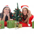 Stock Photo: Two girls in santa hats with presents