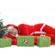 Sleeping santa in red under tree — Stock Photo