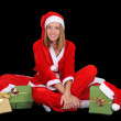 Happy girl in santa costume with presents — Stock Photo