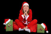 Surprised girl in santa costume with presents — Stock Photo