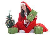 Happy santa with tree holding present — Stock Photo