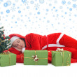 Royalty-Free Stock Photo: Sleeping santa in red under tree