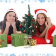 Two girls in santa hats with presents - Stock Photo