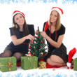 Two girls sitting and decorating the tree - Stock Photo