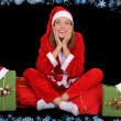 Surprised girl in santa costume with presents - Stock Photo