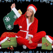 Happy girl in santa costume sitting with presents - Stock Photo