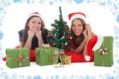 Dvě dívky v santa klobouky s dárky — Stock fotografie