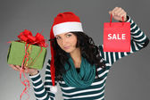 Girl in santa hat and striped dress with gifts — Stock Photo