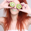 Young woman holding kiwi fruit for her eyes — Stock Photo