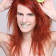 Stock Photo: Attractive redhaired woman with kiwi