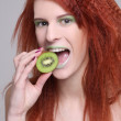 Attractive redhaired girl with biting kiwi — Stock Photo