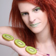 Young redhaired girl with kiwi slices — Stock Photo