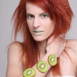 Redhaired girl with kiwi slices on her hand — Stock Photo