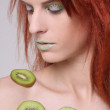 Girl with kiwi slices on her skin — Stock Photo