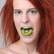 Girl with kiwi slice on her mouth — Stock Photo