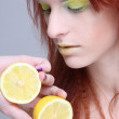 Stock Photo: Young redhaired girl with lemon. close up