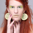 Beautiful redhaired girl with lemon slices in ears — Stock Photo #18683671