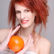 Portrait of redhaired woman with orange — Stock Photo