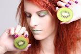 Close up portrait of redhaired girl with kiwi — Stock Photo