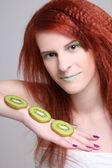 Unga rödhårig tjej med kiwi skivor — Stockfoto