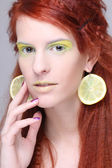 Beautiful girl with lemon slices in ears — Stock Photo